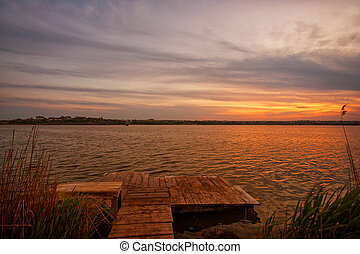 Beautiful sunrise on the lake, with reeds and a fishing bridge in the foreground