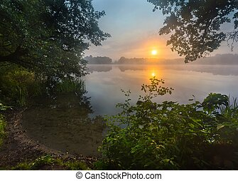 Beautiful sunrise over misty lake.