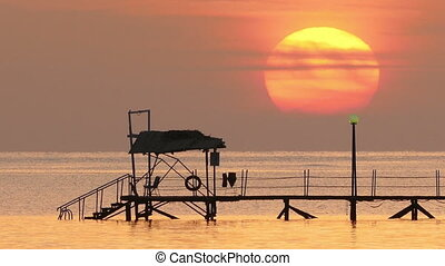 beautiful sunrise over pier in sea - filmed at telephoto...