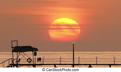 beautiful sunrise over pier in sea - telephoto lens, zoom...