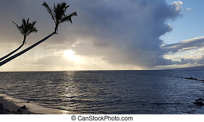 Beautiful Sunrise over the ocean with waves moving to rocky Beach on the Molokai