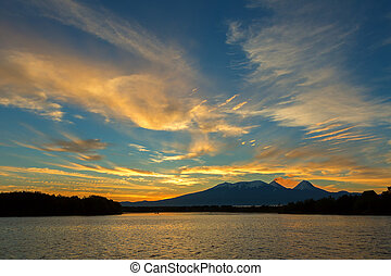Beautiful sunrise over volcanoes Kluchevskaya group with reflection in the river Kamchatka.