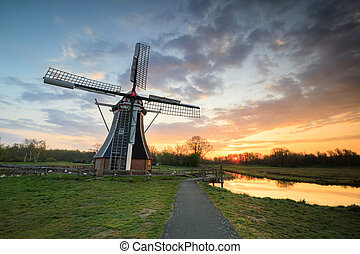 beautiful sunrise over windmill by cycling path