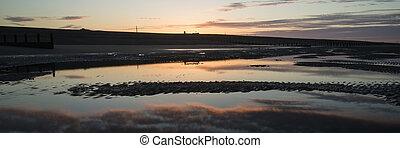 Beautiful sunrise panorama landscape reflected in pools on beach