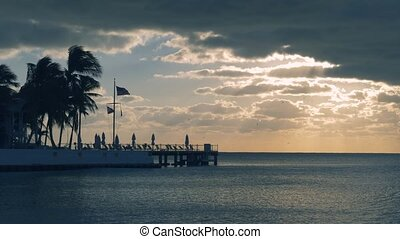 Beautiful sunrise panorama on Key West, Florida, USA. With palms and resorts on background. Sunset over the sea at Key West, Florida. America flag waving in the wind, key west, Florida