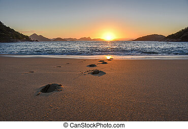 Beautiful sunrise, solar path on water and footprints at the deserted Praia Vermelha Beach