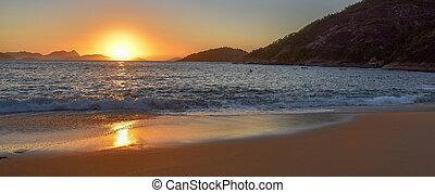 Beautiful sunrise, solar path on water and sand at the deserted Praia Vermelha Beach