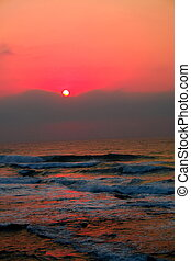 beautiful sunrise on indian ocean with red ligts reflecting...