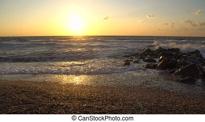 Beautiful sunset above the Black sea with Rocks in Water
