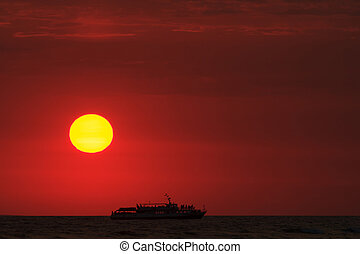 Beautiful sunset and a ship in the sea or ocean