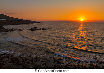Beautiful sunset at a rocky beach in Pomos, Cyprus