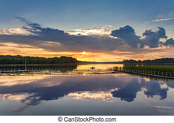Beautiful sunset at the lake with dynamic sky in summer