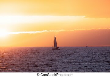 Beautiful sunset at the sea with sailing boat