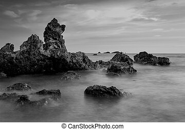 Beautiful sunset at the stone beach in black and white, Thailand