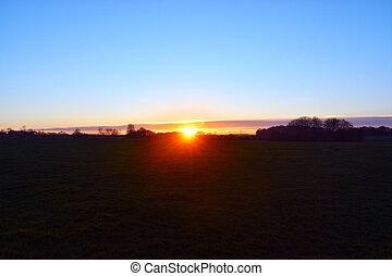 Beautiful sunset, blue sky, silhouette of trees beside to sun shine