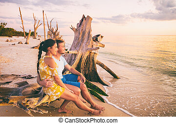 Beautiful sunset honeymoon vacation couple relaxing on summer holiday watching sunset at Florida beach, Gulf of Mexico, USA travel. Man and woman at Lover's key