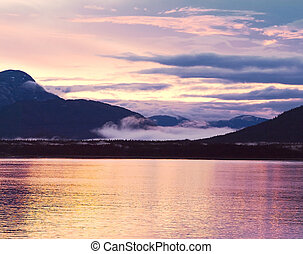 Beautiful Sunset In Alaska. Gold-Purple Reflection In The Water
