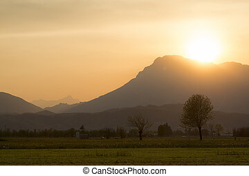 Beautiful sunset in rural area of Meduno, Italy with high mountains on the background.
