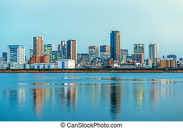 beautiful sunset landscape of Osaka city with modern buildings and river, Japan, panorama