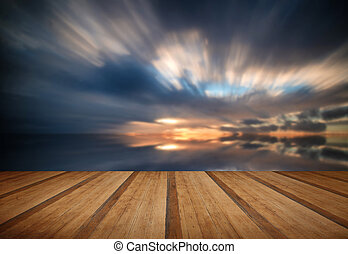 Beautiful sunset long exposure image over ocean with wooden planks floor