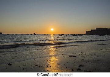 Beautiful sunset on a beach with fishing boats at the bottom, Caleta beach, Cadiz, Spain