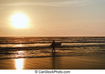 Beautiful sunset on calm sea with surfer silhouette against vibrant deep sky