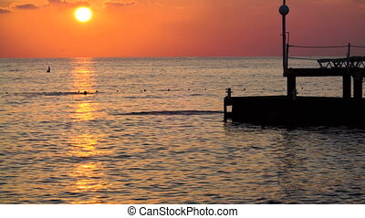 beautiful sunset on sea. silhouette of guy jumping off pier into the Mediterranean sea