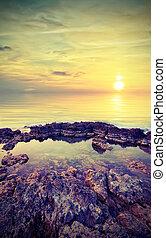 Beautiful sunset on the background of rocks. Vintage style