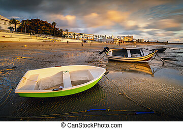 Beautiful sunset on the beach of La Caleta when the tide goes down and the boats that remain static