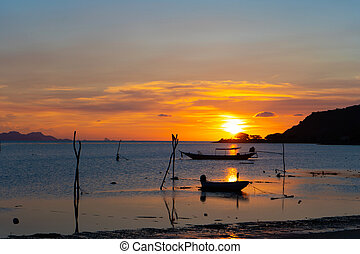 Beautiful sunset on the coast of a tropical island in Thailand, a silhouette of a boat in the ocean