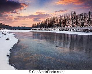 beautiful sunset on the frozen river. location Nealezhnosti...