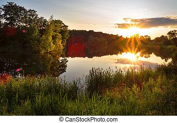 Beautiful sunset on the lake with sunlight.