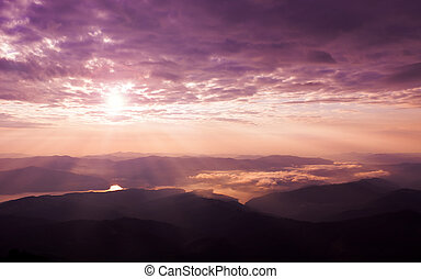 beautiful sunset on the mountain with sun and clouds