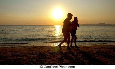 beautiful sunset on the sea. elderly people stroll along the...