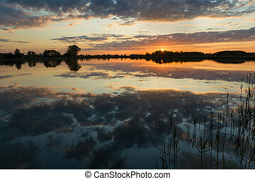Beautiful sunset over a calm lake and reflection of clouds in the water