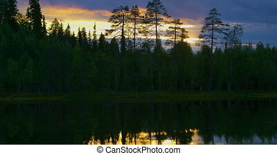 Beautiful sunset over a lake in the finnish forest -...