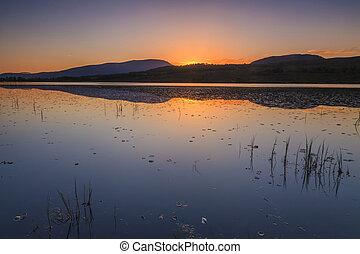 Beautiful sunset over a large mountain lake.