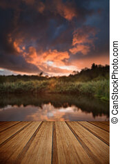 Beautiful sunset over Autumn Fall lake with crystal clear reflections with wooden planks floor