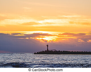 Beautiful sunset over Black sea in Sochi, Russia. Silhouettes of lighthouse and seagulls on the railing.