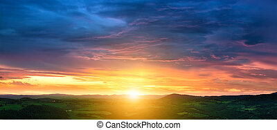 Beautiful sunset over fields and the small town in Tuscany, Italy