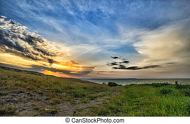 beautiful sunset over lake with cloudy sky