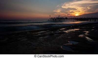 Beautiful sunset over long jetty at the seascape. Timelapse