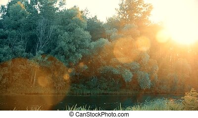 Beautiful sunset over river in summer with lense flare