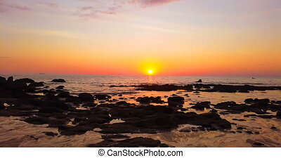 Beautiful sunset over sea with rocks on beach - Timelapse...