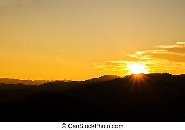 Beautiful sunset over silhouette mountain