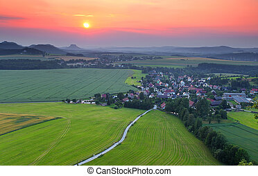 beautiful sunset over small city in saxony mountain