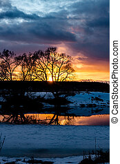 Beautiful sunset over the landscape with a river in March