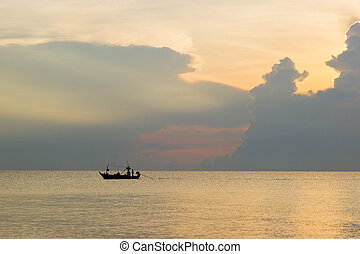 beautiful sunset over the sea and silhouette fishing boat with cloudy sky in Thailand