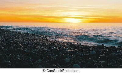 Beautiful Sunset over the Sea near the Stony Shore. Orange...