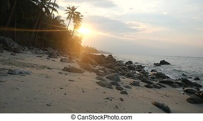 Beautiful sunset over tropical island on rocky beach and palm trees. Waves hit the stones in slow motion. Koh Samui, Thailand.